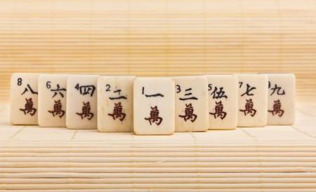 mahjong: Old chinese game mahjongg on bamboo mat background Stock Photo