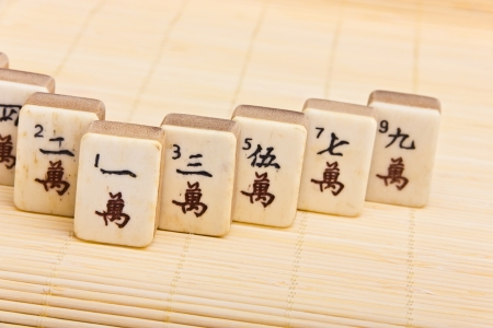 Old chinese game mahjongg on bamboo mat background Stock Photo