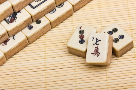 Old chinese game mahjongg on bamboo mat background photo
