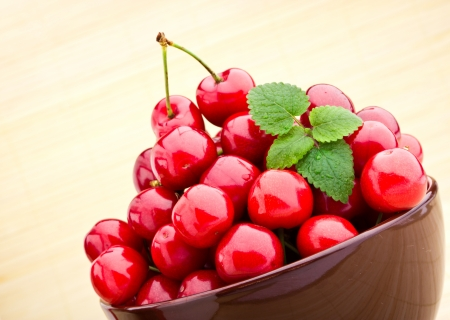 Sweet cherry fruits in brown bowl photo