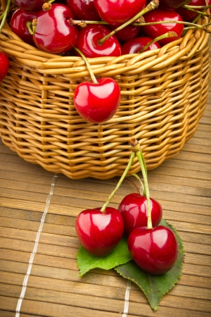 Delicious sweet cherry fruits in wicker basket photo