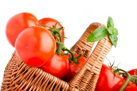 Wicker basket full of delicious tomatoes photo