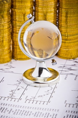 Globe statue on business stock charts and coins background photo