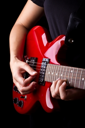 Closeup view of playing electric red guitar photo