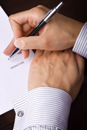 Human hand with pen signing a document photo