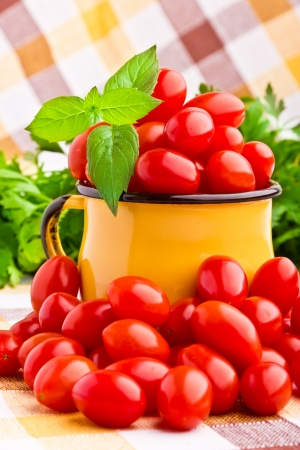 Yellow mug full of fresh cherry tomatoes photo