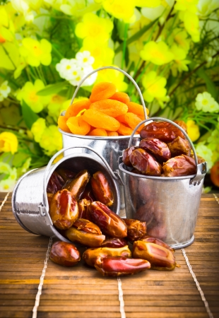 Delicious dried apricots and dates in tin pail photo