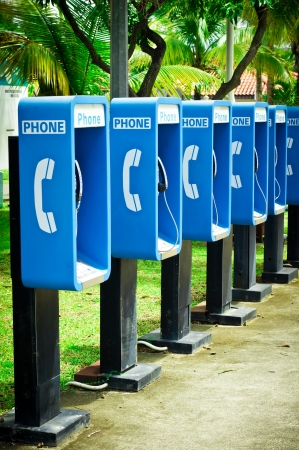 Blue public phone in a row Imagens
