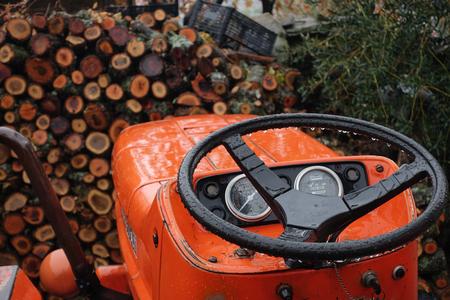 Orange tractor and steering wheel among wood. Banco de Imagens