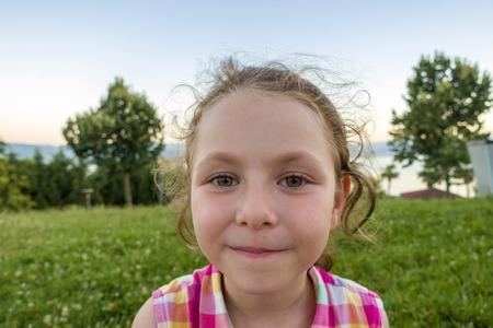 Cute girl child portrait. On grass background. 스톡 콘텐츠