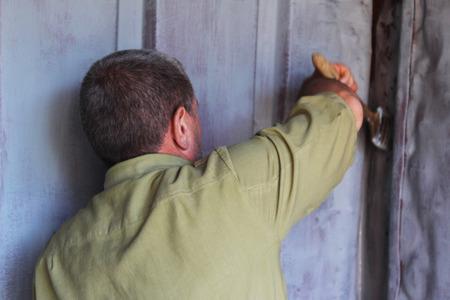 paints: Man paints the walls of iron