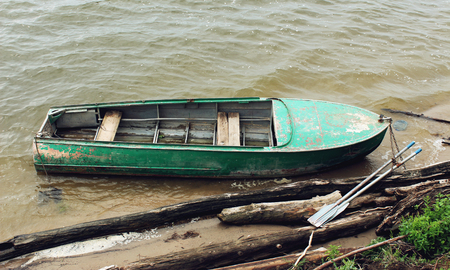 green boat: Old green boat with oars on the coast Stock Photo