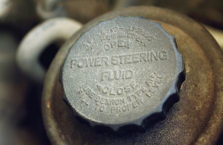 worn: Old worn cap of power steering reservoir