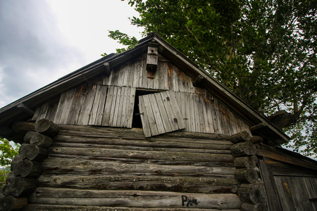 damaged roof: Old abandoned hut in the village