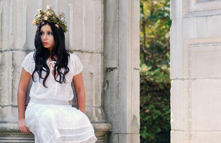 Young woman sitting on a stone pillar photo