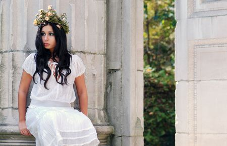 Young woman sitting on a stone pillar Stok Fotoğraf