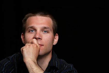 Young man thinking on a black background