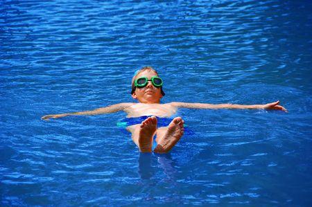 Floating Boy op zijn rug in het blauwe water