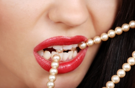 beige lips: woman biting pearl necklace with red lipstick