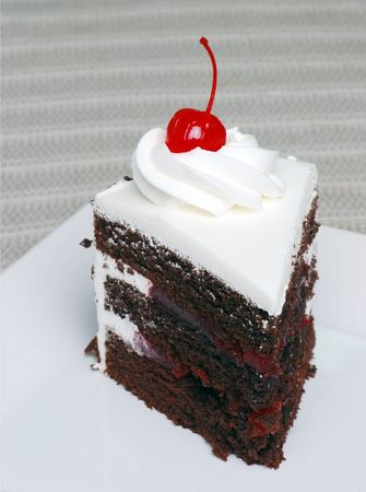 black dish: Slice of chocolate black forest cake with a cherry