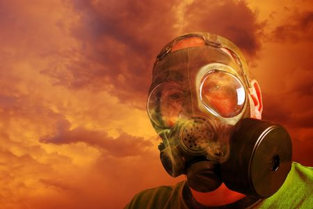 man protecting himself with gas mask from clouds and smoke photo