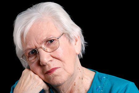 persona confundida: mujer mayor apoyada en la mano con fondo negro Foto de archivo