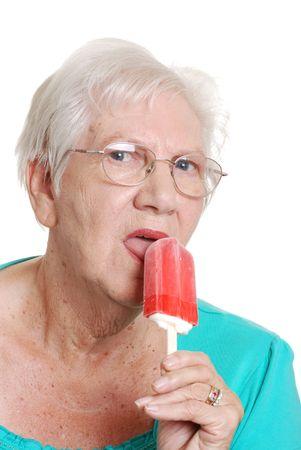 senior woman licking a red ice-cream