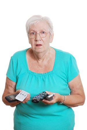 damaged: senior woman confused with lots of tv remotes