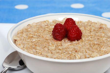 closeup oatmeal with raspberries focus on berries