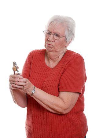 useless: Senior woman struggling to crack a walnut