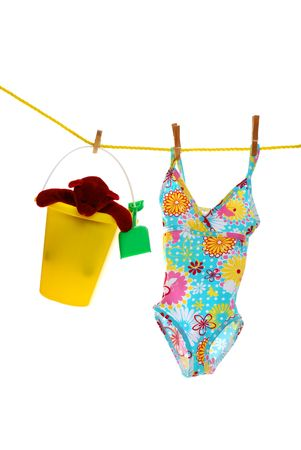 childs bathing suit and toys on clothes line photo