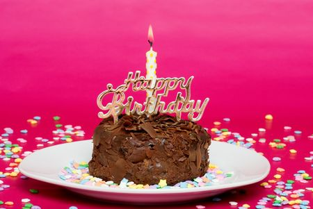 chocolate birthday cake on pink focus at candle photo