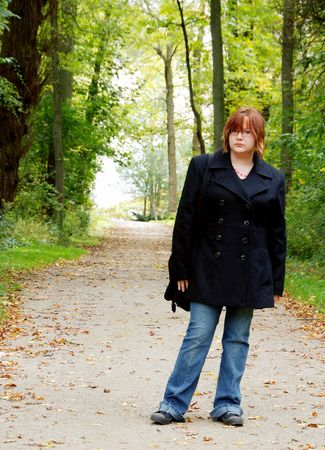 Female teenager on a forest path photo