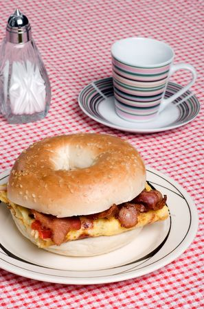 bagel: Omelet with bacon sandwich with coffee