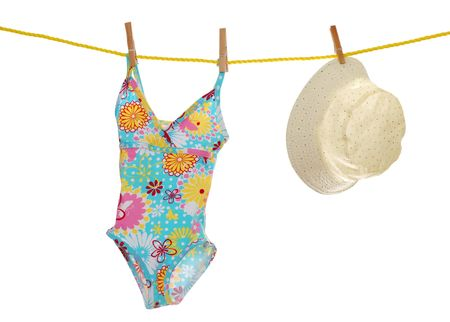 childs bathing suit and beach hat on clothes line photo