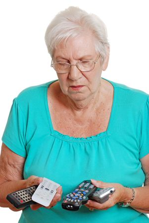 Senior woman confused with so many remote controls photo