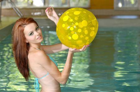 sexy brunette woman hitting a yellow poka dot beac photo