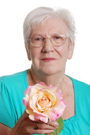 senior woman holding fake rose focus on flower Stock Photo