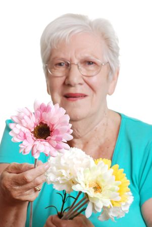 octogenarian:   senior woman offering a fake daisy focus on flower Stock Photo