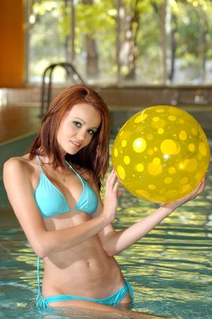 sexy brunette holding a yellow poka dot beach ball