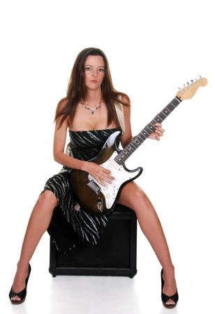sexy brunette sitting on an amplifer with a guitar photo
