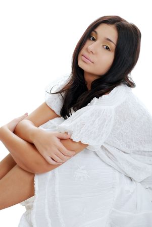 young hispanic woman sitting with arms on her legs photo