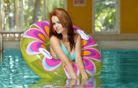 young brunette woman playing in a swimming pool photo