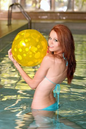 woman in a blue bikini playing with a yellow beachball photo