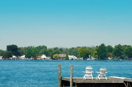 two adirondack chairs on a dock photo
