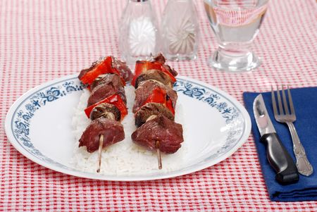 two shish kabobs on a bed of white rice photo
