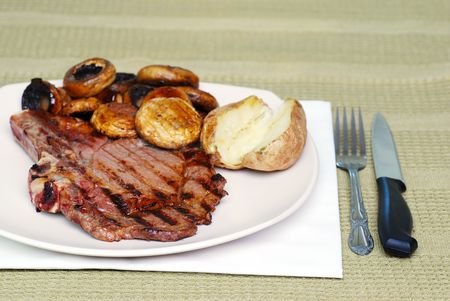 Rib steak with mushrooms and baked potato on a green tablecloth photo