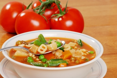 minestrone: vegetable soup with tomato in the background Stock Photo