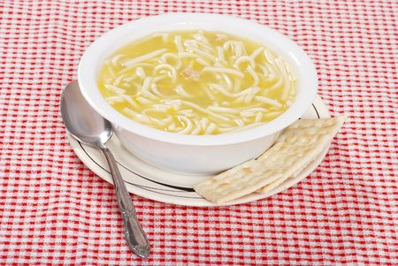 noodle bowl: chicken noodle soup with spoon and crackers