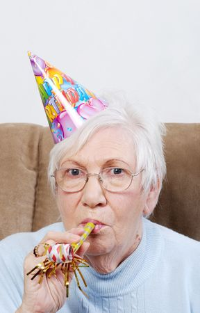 senior woman with birthday hat and noise maker photo